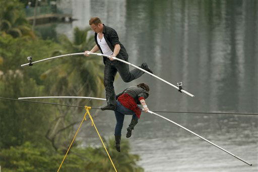 "<div class=""meta ""><span class=""caption-text "">High-wire acrobats Delilah Wallenda, right, lowers her head as her son Nik Wallenda, left, crosses over her during their high-wire act where the two simultaneously walked across a 300-foot-long wire suspended 100 feet in the air between two towers of the Conrad Condado Plaza Hotel in San Juan, Puerto Rico, Saturday June 4, 2011. Nik's great-grandfather, the German-born Karl Wallenda, tried to perform the same feat in 1978 but fell to his death at age 73. The two Wallendas commemorated the famous family patriarch by successfully completing the same stunt Saturday. He was the founder of the ""The Flying Wallendas"" high-wire act.  (AP Photo/Ricardo Arduengo) (AP Photo/ Ricardo Arduengo)</span></div>"