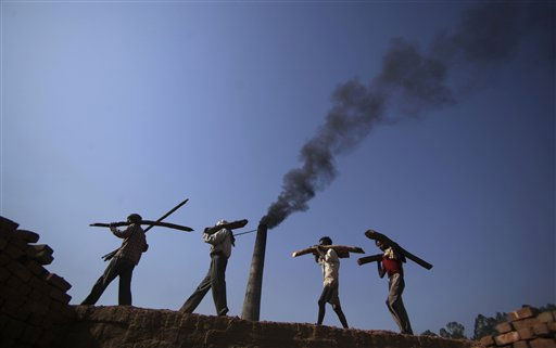 "<div class=""meta ""><span class=""caption-text "">Indian laborers carry firewood, as smoke rises from a brick factory on the outskirts of Jammu, India, Saturday, June 4, 2011. India accounts for 5.5 percent of world greenhouse gas emissions. World Environment Day will be marked on June 5. (AP Photo/Channi Anand) (AP Photo/ Channi Anand)</span></div>"
