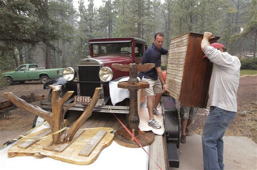 A 1928 Oldsmobile sedan sits in a flatbed trailer as Allan Johnson, right, and Larry Duffy move furniture as they evacuate their home in Greer, Ariz., Sunday, June 5, 2011. Crews used controlled backfires early Sunday to blunt the advance of a major wildfire near mountain communities in eastern Arizona, a blaze termed &#34;absolutely frightening&#34; by the state&#39;s governor that has already burned through 225 square miles of forest and brush. &#40;AP Photo&#47;Jae C. Hong&#41; <span class=meta>(AP Photo&#47; Jae C. Hong)</span>