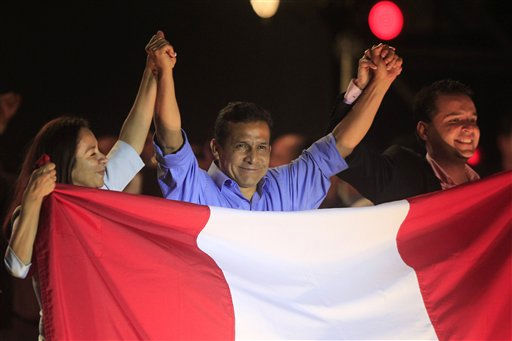 Peru&#39;s presidential candidate Ollanta Humala, center, raises hands with his running mates First Vice President Marisol Espinoza, left, and Second Vice President Omar Chehade after the presidential runoff election in Lima, Peru, Sunday June 5, 2011. Humala declared victory over rival candidate Keiko Fujimori in Peru&#39;s tightly contested presidential runoff, with official results incomplete but showing him winning. &#40;AP Photo&#47;Martin Mejia&#41; <span class=meta>(AP Photo&#47; Martin Mejia)</span>