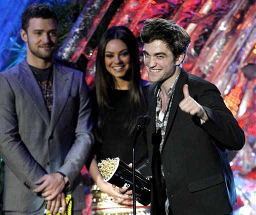Robert Pattinson accepts the award for best male performance at the MTV Movie Awards on Sunday, June 5, 2011, in Los Angeles. In background looking on are presenters Justin Timberlake and Mila Kunis. &#40;AP Photo&#47;Matt Sayles&#41; <span class=meta>(AP Photo&#47; Matt Sayles)</span>