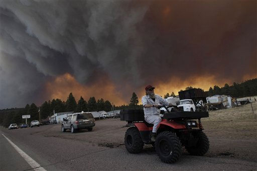 Robert Joseph, 64, rides his ATV as smoke plumes from the Wallow fire fill the sky in Luna, N.M., Monday, June 6, 2011. Firefighters worked furiously Monday to save a line of mountain communities in eastern Arizona from a gigantic blaze that has forced thousands of people from their homes and cast a smoky haze over states as far away as Iowa. &#40;AP Photo&#47;Jae C. Hong&#41; <span class=meta>(AP Photo&#47; Jae C. Hong)</span>