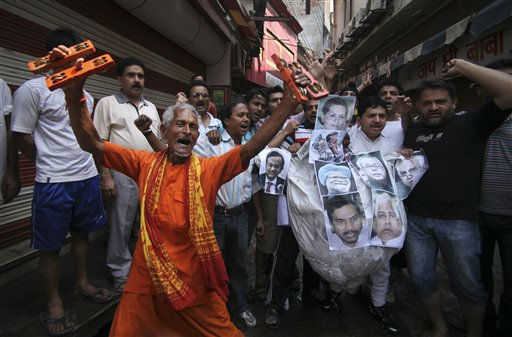 A Hindu priest along with supporters of Indian yoga guru Baba Ramdev shout slogans before burning an effigy with portraits of Indian Prime Minister Manmohan Singh, center, Congress party President Sonia Gandhi, top, and other lawmakers, during a protest in Jammu, India, Wednesday, June 8, 2011. The supporters were protesting against the forceful eviction of Ramdev and his followers from a protest camp against corruption in New Delhi. Police swooped down on the protest camp early Sunday, using tear gas to break it up and triggering a stampede and clashes with rock-throwing protesters that left dozens injured on both sides. &#40;AP Photo&#47;Channi Anand&#41; <span class=meta>(AP Photo&#47; Channi Anand)</span>