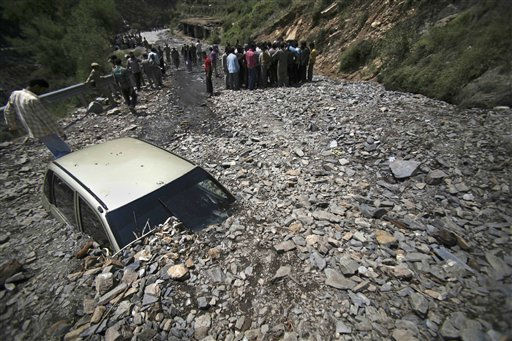 A car lies covered with rubble from a landslide after a cloudburst in Doda district, about 140 kilometers &#40;88 miles&#41; from Jammu, India, Thursday, June 9, 2011. At least four people were feared dead and hundreds of vehicles stranded after a cloudburst on the Doda-Batote highway Thursday, according to government officials. &#40;AP Photo&#47;Channi Anand&#41; <span class=meta>(AP Photo&#47; Channi Anand)</span>