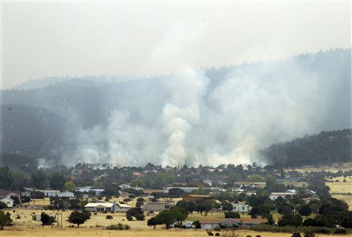 "<div class=""meta image-caption""><div class=""origin-logo origin-image ""><span></span></div><span class=""caption-text"">Smoke from the Wallow Fire rises over a neighborhood in Eagar, Ariz., Thursday, June 9, 2011. A spot fire at the edge of the larger blaze prompted the few residents left in Springerville and the neighboring community of Eagar to flee. (AP Photo/Marcio Jose Sanchez) (AP Photo/ Marcio Jose Sanchez)</span></div>"