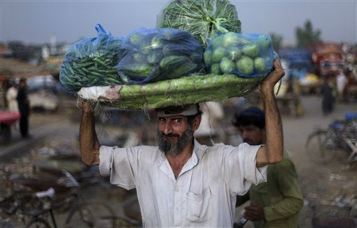 Pakistani Aslam Hazrat, 63, while carrying a customer&#39;s vegetables over his head at a wholesale fruit and vegetable market on the outskirts of Islamabad, Pakistan, Friday, June 10, 2011. &#40;AP Photo&#47;Muhammed Muheisen&#41; <span class=meta>(AP Photo&#47; Muhammed Muheisen)</span>