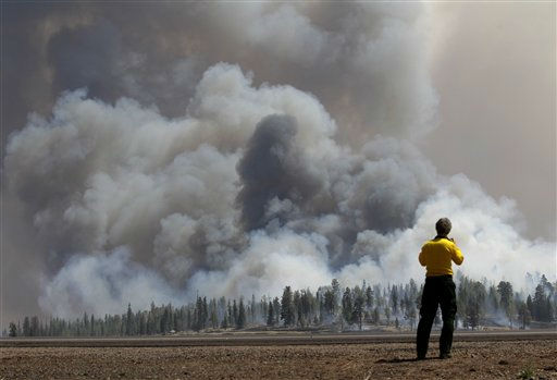 A photographer looks at smoke from a burnout fire as firefighters battle the Wallow Fire in the Apache-Sitgreaves National Forest, Ariz., Sunday, June 12, 2011. Roughly 7,000 residents of two eastern Arizona towns evacuated last week as a wildfire loomed nearby were allowed to return home Sunday as officials expressed confidence that they were making progress in their battle against the huge blaze that has been burning since May. &#40;AP Photo&#47;Jae C. Hong&#41; <span class=meta>(AP Photo&#47; Jae C. Hong)</span>