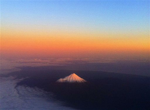 New Zealand&#39;s Mount Taranaki has a warm glow lighting the snow peak as an ash cloud from a Chilean volcano drifts across the Pacific, Sunday, June 12, 2011. Most airlines grounded more flights to and from southern Australia and New Zealand on Monday morning after an ash cloud from the Cordon Caulle volcano in southern Chile expanded overnight. &#40;AP Photo&#47;David Frampton&#41; NEW ZEALAND OUT, EDITORIAL USE ONLY <span class=meta>(AP Photo&#47; David Frampton)</span>