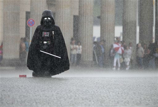 A Darth Vader actor waits for tourists who want to be photographed together with him, in front of the Brandenburg Gate during a thunderstorm in Berlin, Germany, Tuesday, June 14, 2011. &#40;AP Photo&#47;Michael Sohn&#41; <span class=meta>(AP Photo&#47; Michael Sohn)</span>