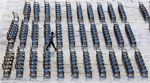 A worker walks among empty chairs before the groundbreaking ceremony for a museum in Seoul, South Korea, Wednesday, June 15, 2011. &#40;AP Photo&#47;Lee Jin-man&#41; <span class=meta>(AP Photo&#47; Lee Jin-man)</span>