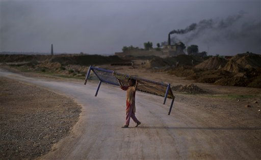Pakistani Nagina Sadiq, 8, crosses a street carrying a bed over her head, heading to a brick factory, where she and her family work, on the outskirts of Islamabad, Pakistan, Wednesday, June 15, 2011. &#40;AP Photo&#47;Muhammed Muheisen&#41; <span class=meta>(AP Photo&#47; Muhammed Muheisen)</span>