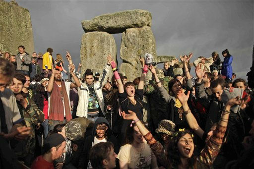 Revellers cheer as the sun finally breaks through the clouds more than a couple of hours after sunrise during the summer solstice at Stonehenge, near Salisbury in England, Tuesday, June 21, 2011.  The ancient stone circle of Stonehenge is a World Heritage Site erected between approximately 3000BC and 1600BC and despite years of research the reason behind its construction remains a mystery. The summer solstice in the northern hemisphere occurs annually on June 21 and is the time at which the sun is at its northernmost point in the sky.  &#40;AP Photo&#47;Matt Dunham&#41; <span class=meta>(AP Photo&#47; Matt Dunham)</span>