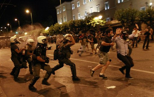 Greek riot police officers charge protesters at Syntagma square in front of the Greek Parliament in central Athens, during minor scuffles following a peaceful ongoing rally against plans for new austerity measures, early Wednesday, June 22, 2011. Demonstrators had camped outside parliament since May 25, 2011. &#40;AP Photo&#47;Lefteris Pitarakis&#41; <span class=meta>(AP Photo&#47; Lefteris Pitarakis)</span>