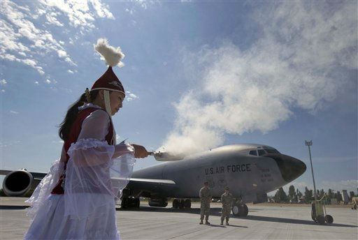 A Kyrgyz woman performs a traditional ritual during a ceremony of the opening of a new large aircraft ramp at the US Army base on Thursday, June 23, 2011, at the Manas International Airport, Kyrgyzstan. The new large aircraft ramp was opened after 17 months of designing, planning, coordinating and constructing. &#40;AP photo&#47;Vladimir Voronin&#41; <span class=meta>(AP Photo&#47; Vladimir Voronin)</span>