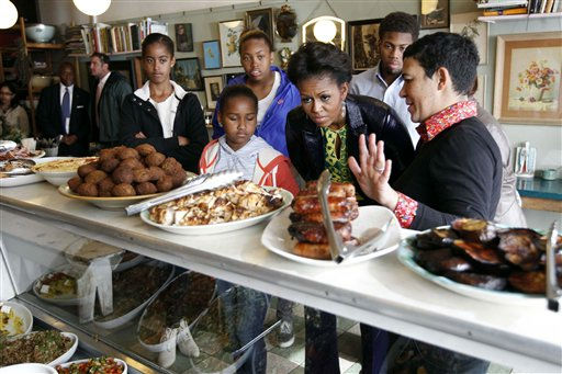 U.S. first lady Michelle Obama stands with Karen Dudley, right, at her restaurant &#34;The Kitchen&#34; as she makes an unscheduled stop for lunch in Cape Town, South Africa, Thursday, June 23, 2011. Also pictured, left to right,  daughters Malia and Sasha Obama, niece Leslie Robinson, nephew Avery Robinson. &#40;AP Photo&#47;Charles Dharapak, Pool&#41; <span class=meta>(Photo&#47;Charles Dharapak)</span>