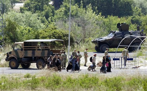 "<div class=""meta ""><span class=""caption-text "">Syrians refugees pass Turkish military vehicles as they cross the border at a crossing point near the Turkish village of Guvecci in Hatay province, Turkey, Thursday, June 23, 2011. Syrian activists claimed that troops backed by tanks and snipers have entered a village along the Turkish border as the regime expands its crackdown on a pro-democracy movement that has posed the gravest challenge to President Bashar Assad's rule.(AP Photo/Burhan Ozbilici) (AP Photo/ Burhan Ozbilici)</span></div>"