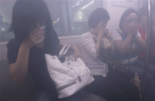 South Koreans cover their mouths against smoke filling inside a subway train during a disaster prevention drill in Seoul, South Korea, Friday, June 24, 2011. &#40;AP Photo&#47;Ahn Young-joon&#41; <span class=meta>(AP Photo&#47; Ahn Young-joon)</span>