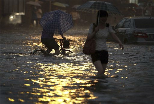 Chinese people wade through a flooded road during a heavy rain storm in Beijing, China, Thursday, June 23, 2011. Parts of Beijing have been flooded by torrential rain, and airport officials say the downpour forced the cancellation of 150 flights Thursday. &#40;AP Photo&#47;Color China Photo&#41; CHINA OUT <span class=meta>(AP Photo&#47; AW TT**TOK**)</span>