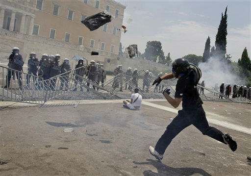 "<div class=""meta image-caption""><div class=""origin-logo origin-image ""><span></span></div><span class=""caption-text"">A protester throws a garbage bag to riot police in front of the Greek Parliament during clashes in central Athens Wednesday, June 29, 2011.Greek deputies are to vote Wednesday on a deeply unpopular austerity bill that has provoked days of rioting in the streets of Athens, with the result of the vote determining is Greece can avoid a potentially disastrous financial default in the coming weeks .(AP Photo/Petros Giannakouris) (AP Photo/ Petros Giannakouris)</span></div>"