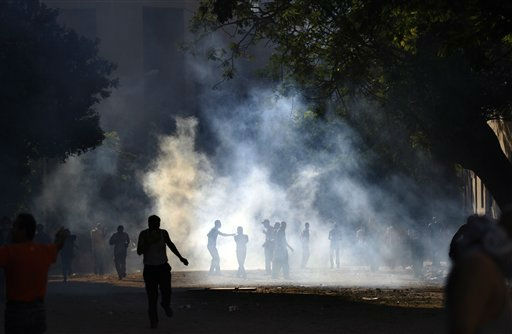Demonstrators are seen through the haze of tear gas during clashes with the Egyptian security close to the interior ministry in Cairo, Egypt, early Wednesday, June 29, 2011. Egyptian security forces and protesters are clashing for a second successive day in central Cairo in scenes not seen since the uprising that toppled Hosni Mubarak earlier this year.  &#40;AP Photo&#47;Khalil Hamra&#41; <span class=meta>(AP Photo&#47; Khalil Hamra)</span>