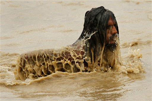 A Hindu holy man takes a dip in the River Ganges, which appears muddy and swollen after heavy rains in upstream areas, in Allahabad, Thursday, June 30, 2011. &#40;AP Photo&#47;Rajesh Kumar Singh&#41; <span class=meta>(AP Photo&#47; Rajesh Kumar Singh)</span>