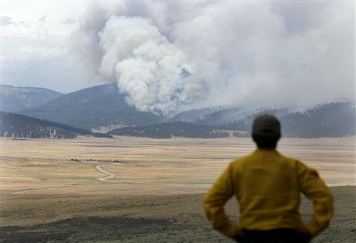 A television producer watches smoke from the Las Conchas fire near Los Alamos, N.M., Thursday, June 30, 2011. With firefighters bracing for another day of strong, erratic winds, the wildfire near the nation&#39;s premier nuclear weapons laboratory and a northern New Mexico community was poised to become the largest forest fire in state history. &#40;AP Photo&#47;Jae C. Hong&#41; <span class=meta>(AP Photo&#47; Jae C. Hong)</span>