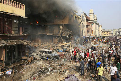 People gather at the site of a fire on Lagos Island in Lagos, Nigeria, on Wednesday, Dec. 26, 2012. An explosion ripped through a warehouse Wednesday where witnesses say fireworks were  stored in Nigeria&#39;s largest city, sparking a fire. It wasn&#39;t immediately clear if anyone was injured in the blast that firefighters and locals struggled to contain. &#40;AP Photo&#47;Jon Gambrell&#41; <span class=meta>(AP Photo&#47; Jon Gambrell)</span>