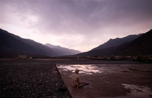 An Afghan man prays at sunset on the helipad following a rain storm Sunday, July 3, 2011 at Forward Operating Base Bostick in Kunar province, Afghanistan. &#40;AP Photo&#47;David Goldman&#41; <span class=meta>(AP Photo&#47; David Goldman)</span>