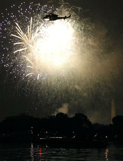 "<div class=""meta ""><span class=""caption-text "">A helicopter flies by as fireworks illuminate the night sky and are reflected in the Potomac River with the Washington Monument at right on Monday, July 4, 2011 in Washington. (AP Photo/Alex Brandon) (AP Photo/ Alex Brandon)</span></div>"