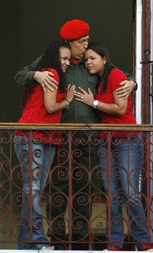 CORRECTS NAME OF DAUGHTER AT RIGHT -- Venezuela&#39;s President Hugo Chavez kisses his daughter Maria Gabriela, right, and embraces daughter Rosa Virginia after greeting supporters at a balcony of Miraflores presidential palace in Caracas, Venezuela, Monday, July 4, 2011. Chavez returned to Venezuela from Cuba on Monday morning, stepping off a plane hours before dawn and saying he is feeling better as he recovers from surgery that removed a cancerous tumor. &#40;AP Photo&#47;Ariana Cubillos&#41; <span class=meta>(AP Photo&#47; Ariana Cubillos)</span>