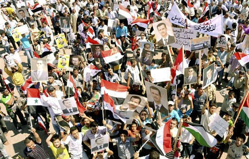 "<div class=""meta image-caption""><div class=""origin-logo origin-image ""><span></span></div><span class=""caption-text"">In this photo released by the Syrian official news agency SANA, Syrian supporters of President Bashar Assad carry his pictures along national flags and banners during a rally in the northern city of Aleppo, Syria, Tuesday, July 5, 2011. A Syrian activist says buses carrying security forces have been spotted heading to restive, mountainous areas near the Turkish border. President Bashar Assad has unleashed a military siege in the area to prevent the opposition from establishing a base. (AP Photo/SANA) EDITORIAL USE ONLY (AP Photo/ HO)</span></div>"