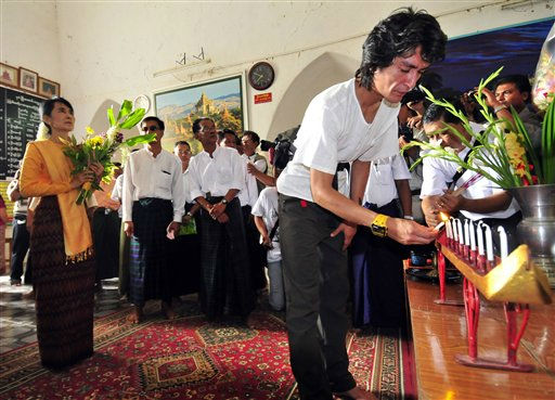 "<div class=""meta ""><span class=""caption-text "">Myanmar democracy icon Aung San Suu Kyi, left, offers flowers as her youngest son Kim Aris, front right, lights candles during their visit to a pagoda in Bagan, Myanmar, Tuesday, July 5, 2011. Suu Kyi visited the ancient city of temples and met with her youngest son during her first trip into the countryside since her release from house arrest in Yangon in November. (AP Photo/Khin Maung Win) (AP Photo/ Khin Maung Win)</span></div>"