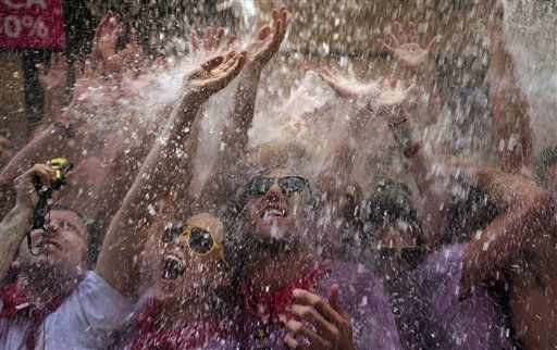 Revelers react as water is thrown from a balcony during the &#39;Chupinazo&#39;, the official opening of the San Fermin fiestas in Pamplona, northern Spain, Wednesday, July 6, 2011. The fiestas &#39;Los San Fermines&#39; held since 1591, attracts tens of thousands of foreign visitors each year for nine days of revelry, morning bull-runs and afternoon bullfights. &#40;AP Photo&#47;Alvaro Barrientos&#41; <span class=meta>(AP Photo&#47; Alvaro Barrientos)</span>