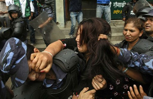 A Tibetan exile tussles with Nepalese police officers as she is prevented from proceeding to the venue where a birthday celebration for spiritual leader the Dalai Lama is being held, in Katmandu, Nepal, Wednesday, July 6, 2011. Nepalese authorities prevented exiled Tibetans from celebrating the Dalai Lama&#39;s birthday on Wednesday over concerns that gatherings will turn anti-Chinese. &#40;AP Photo&#47;Binod Joshi&#41; <span class=meta>(AP Photo&#47; Binod Joshi)</span>
