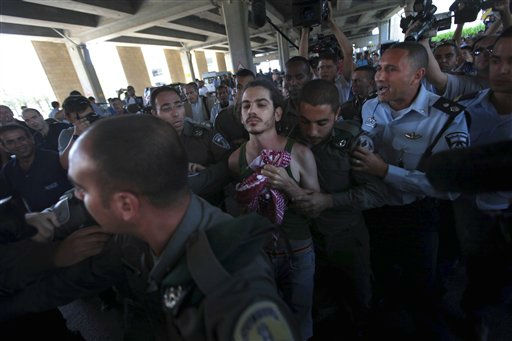 "<div class=""meta ""><span class=""caption-text "">A locally-based pro-Palestinian activist is detained by Israeli police forces after protesting at Ben-Gurion international airport near Tel Aviv, Israel Friday, July 8, 2011. Scores of pro-Palestinian protesters trying to reach Israel were blocked at airports in Europe and two American activists who arrived in Israel were deported early Friday, Israeli officials said, after Israel increased security at the airport ahead of the activists' arrival and asked foreign airlines to prevent blacklisted travelers from boarding Israel-bound flights. (AP Photo/Oded Balilty) (AP Photo/ Oded Balilty)</span></div>"
