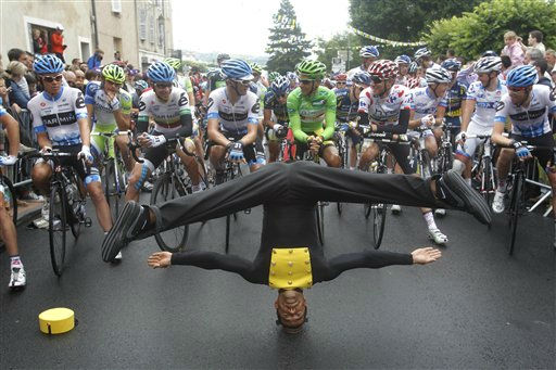 An etertainer does a balancing act as the pack waits to take the start of the 9th stage of the Tour de France cycling race over 208 kilometers &#40;129 miles&#41; starting in Issoire and finishing in Saint Flour, central France, Sunday July 10, 2011. &#40;AP PhotoChristophe Ena&#41; <span class=meta>(AP Photo&#47; Christophe Ena)</span>