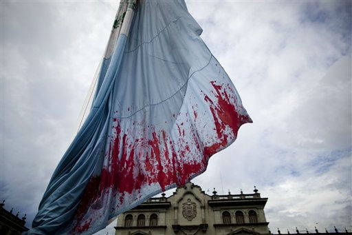 A Guatemalan flag with red stains symbolizing the blood of murdered Argentine artist Facundo Cabral, hangs at half staff during a demonstration in Guatemala City, Sunday, July 10, 2011. One of Latin America&#39;s most admired folk singers, Facundo Cabral, was killed July 9 when three cars loaded with gunmen ambushed the vehicle in which he was riding, prompting expressions of anguish from across the region. Authorities said the performer&#39;s concert promoter who was traveling with Cabral was apparently the target. &#40;AP Photo&#47;Rodrigo Abd&#41; <span class=meta>(AP Photo&#47; Rodrigo Abd)</span>