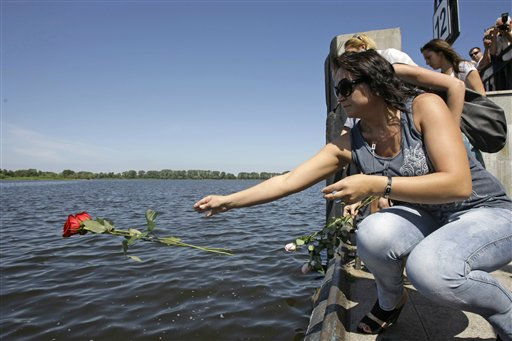 People throw flowers into the port of Kazan, Russia, Tuesday, July 12, 2011, on the Volga River, in central Russia. Russia is observing a day of mourning for victims of a cruise ship sinking as divers work deep underwater in a Volga River reservoir to try to find more bodies. The 55-year-old double-decker boat was carrying 208 people when it sank Sunday, a load about 75 percent more than it was licensed to carry.  &#40;AP Photo&#47;Misha Japaridze&#41; <span class=meta>(Photo&#47;Misha Japaridze)</span>