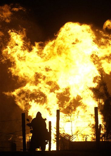 An Egyptian sitting astride his motorbike watches the leaping flames after masked gunmen blew up a terminal of the Egyptian natural gas pipeline to Israel and Jordan in El Arish,in the northern part of Egypt&#39;s Sinai Peninsula, early, Tuesday, July 12 2011, Security officials say. &#40;AP Photo&#41; <span class=meta>(AP Photo&#47; Anonymous)</span>