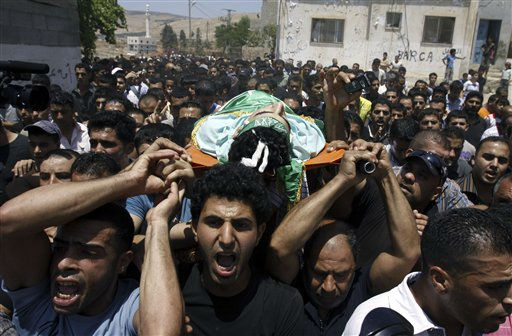 Palestinians carry the body of Ibrahim Sarhan, killed by Israeli military, during his funeral in the West Bank refugee camp of El Fara, north of Nablus, Wednesday, July 13, 2011.  Sarhan was killed Wednesday in an Israeli military raid on a West Bank refugee camp, Palestinians said, when Israeli troops had entered the El Fara camp in pursuit of a fugitive militant. According to witnesses residents began throwing stones at the troops, who responded with live fire, killing Sarhan.&#40;AP Photo&#47;Mohammed Ballas&#41; <span class=meta>(AP Photo&#47; Mohammed Ballas)</span>