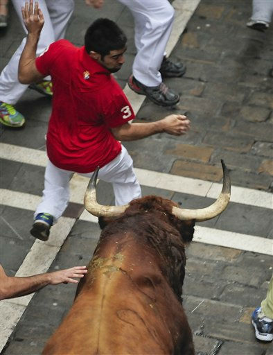 Reveler runs beside a Pilar ranch bull on the Estafeta street during the seventh running of the bulls at the San Fermin fiestas in Pamplona northern Spain, Wednesday July 13, 2011. &#40;AP Photo&#47;Alvaro Barrientos&#41; <span class=meta>(AP Photo&#47; Alvaro Barrientos)</span>