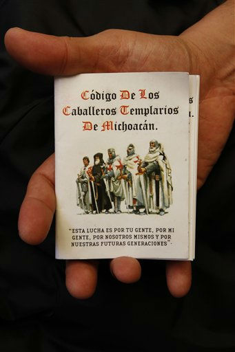 "<div class=""meta image-caption""><div class=""origin-logo origin-image ""><span></span></div><span class=""caption-text"">A man holds up a copy of the 'The Code of the Knights Templar of Michoacan',  in Morelia, Mexico, Tuesday, July 19, 2011. The professionally printed, pocket-size booklet was obtained by the Associated Press by a person who did not want to be identified and who said it was distributed earlier this month by two men in regular clothing aboard a bus traveling in rural Michoacan. (AP Photo/Marco Ugarte) (AP Photo/ Marco Ugarte)</span></div>"