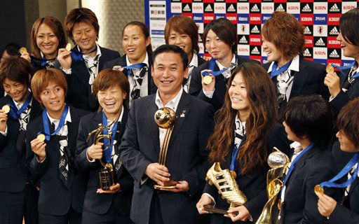 Japanese women&#39;s national soccer team coach Norio Sasaki, center, holding the World Cup trophy, poses with team players including captain Homare Sawa, third right bottom, and Aya Miyama, third left bottom, during a press conference in Tokyo, Tuesday, July 19, 2011. Japan beat the U.S. in the final match at the Women&#39;s Soccer World Cup in Frankfurt, Germany on Sunday, July 17. &#40;AP Photo&#47;Koji Sasahara&#41; <span class=meta>(AP Photo&#47; Koji Sasahara)</span>