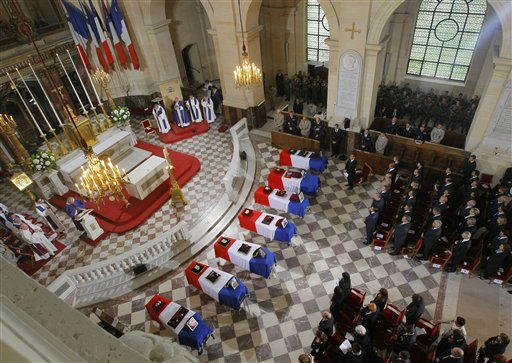 French President Nicolas Sarkozy, center, stands at flag-draped coffins inside the Invalides church as tribute is paid by France to the seven French soldiers killed last week in Afghanistan during a national ceremony in Paris, Tuesday, July 19, 2011. Last week was one of the deadliest for French troops since the operation began in 2001. The seven soldiers killed were honored in a somber funeral ceremony at the site of Napoleon&#39;s tomb in central Paris. &#40;AP Photo&#47;Jacques Brinon, Pool&#41; <span class=meta>(AP Photo&#47; Jacques Brinon)</span>