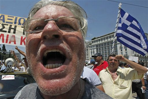 Striking taxi drivers shout anti-government slogans outside the Greek Parliament in Athens, during a protest Tuesday, July 19, 2011. Taxi drivers are angry at plans to liberalize their tightly-regulated profession, as part of the country&#39;s fiscal recovery program that has already spurred months of protests from other affected professional groups. The banner reads in Greek &#34;no to the devaluation of the taxi&#34; &#40;AP Photo&#47;Dimitri Messinis&#41; <span class=meta>(AP Photo&#47; Dimitri Messinis)</span>