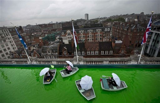 Curator Sam Bompas, left, poses for photographers on a boating lake with dyed green water, which forms part of his installation on the roof of the Selfridges department store on Oxford Street, in London, Thursday, July 21, 2011.  Selfridges will open up its roof to the public, for just the second time since World War II, to host the installation conceived by the artists Bompas &amp; Parr.  The top of The London Eye, and Houses of Parliament seen on horizon at left. &#40;AP Photo&#47;Matt Dunham&#41; <span class=meta>(AP Photo&#47; Matt Dunham)</span>