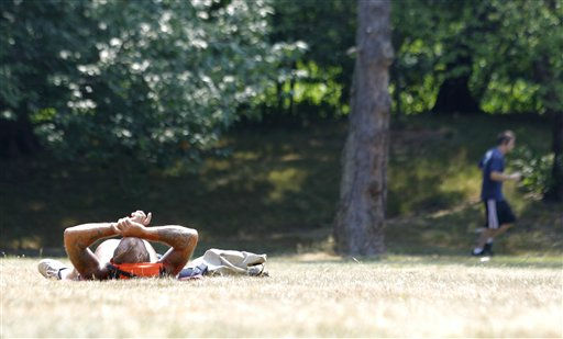 A jogger, right, is seen exercising as Wayne Sarra, 54, of Bloomfield, N.J., sun bathes at Branch Brook Park, Thursday, July 21, 2011, in Newark, N.J. &#34;I hate that winter, I rather have this any time,&#34; said Sarra about the heat wave that is hitting the North New Jersey region with temperatures nearing the triple digit mark. &#40;AP Photo&#47;Julio Cortez&#41; <span class=meta>(AP Photo&#47; Julio Cortez)</span>