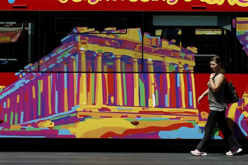 A woman passes next to a tourist bus covered with a picture of the ancient Parthenon temple in central Athens, on Thursday, July 21, 2011.  Despite last year&#39;s 110 billion euros &#40;&#36;156 billion&#41; bailout deal from its European partners and the International Monetary Fund, Greece is looking for another debt relief program, which  EU leaders are meeting to discuss in Brussels Thursday.&#40;AP Photo&#47;Petros Giannakouris&#41; <span class=meta>(AP Photo&#47; Petros Giannakouris)</span>