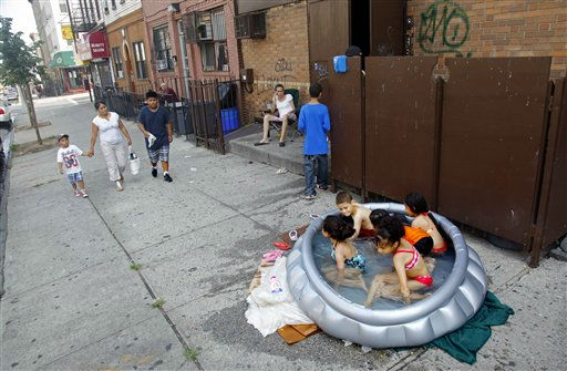Stephanie Gracia, center, sit nearby and watch as her children and their friends cool off in an inflatable pool outside their apartment on Thursday, July 21, 2011, in the Bushwick section of Brooklyn, New York.  A heat wave that has enveloped much of the central part of the country for the past couple of weeks has moved east with temperatures  topping 100-degree.  &#40;AP Photo&#47;Bebeto Matthews&#41; <span class=meta>(AP Photo&#47; Bebeto Matthews)</span>