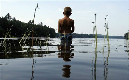 Tyler Carter, 6, of Auburn, Maine, wades in Sabbathday Lake to fish for bass, in New Gloucester, Maine, Thursday, July 21, 2011. The heat that has gripped much of the nation moved into Maine on Thursday as temperatures climbed into the 90s. &#40;AP Photo&#47;Robert F. Bukaty&#41; <span class=meta>(AP Photo&#47; Robert F. Bukaty)</span>